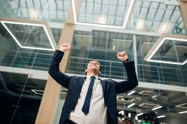 businessman with arms up celebrating his victory