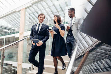 Three multiracial business people walking down on stairs with digital tablet