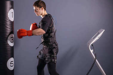 man in boxing gloves during training. boxer in suit of electric stimulation