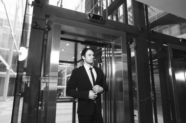 middle aged businessman with briefcase coming out from elevator