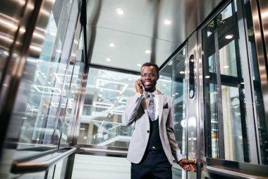 afroamerican businessman in modern glass elevator talking on phone