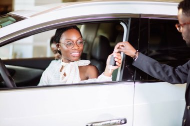 Sales situation in car dealership, young african couple gets the key for new car