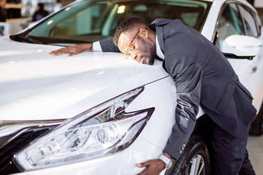 Handsome black man is hugging his new car and smiling