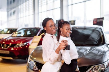 two african american woman near car with keys in hand - concept of buying car