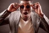 Fotografie shot of amazing Afro male with funny sun glasses and wide opened mouth in suit