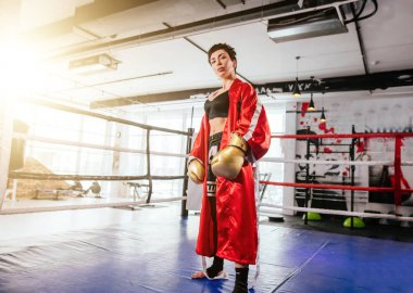 formidable wonan in sporty equipment for boxing looking at camera on ring at gym