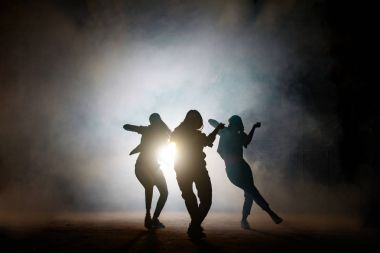 Group of young female dancers on the street at night