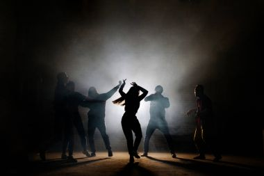 teenagers making dancing moves isoleted on the black background