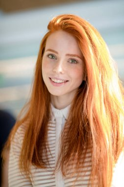 ginger female with long straight shiny hair and natural make-up smiling