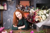 Photo saleswoman with ginger hair working with flowers in flower shop