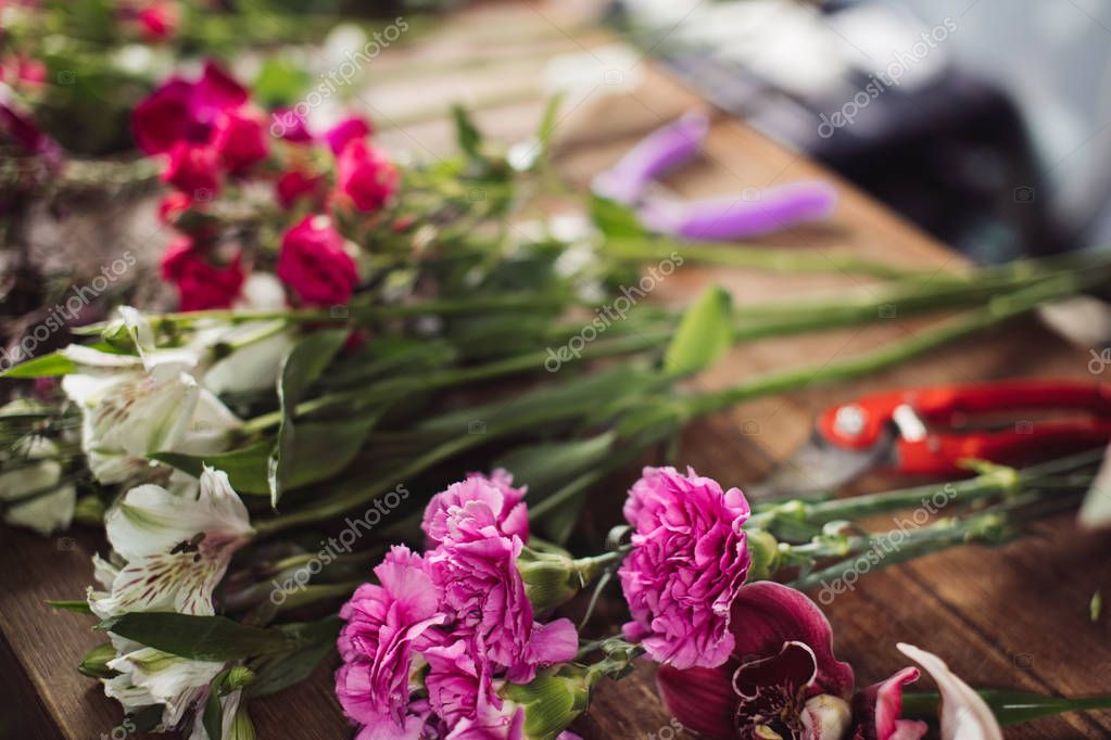 red, white, pink flowers lying on the desk at flower shop