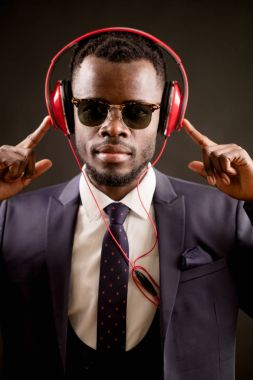 handsome African male holding his headphones and listening to the music