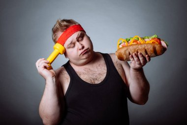 fat man looking at camera and holding burger and dumbbell