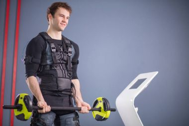 Man working out EMS training with barbell closeup, power pose