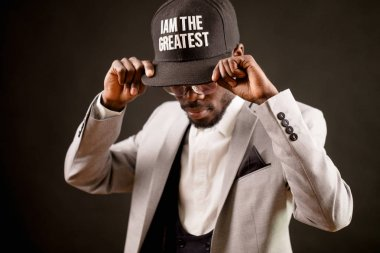 modest Afro man with a cap with inscription I am the greatest