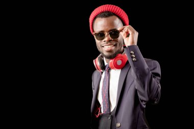 singer with beard wearing stylish outfit in sunglasses, red headphones and cap