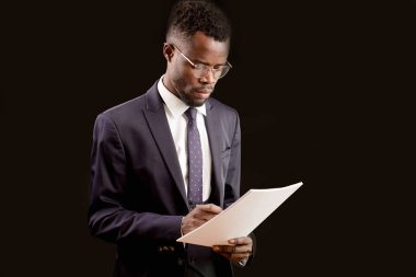 young good-looking energetic business man is writing on documents