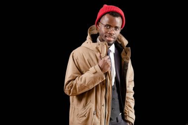 young African man in winter clothes isolated on black background
