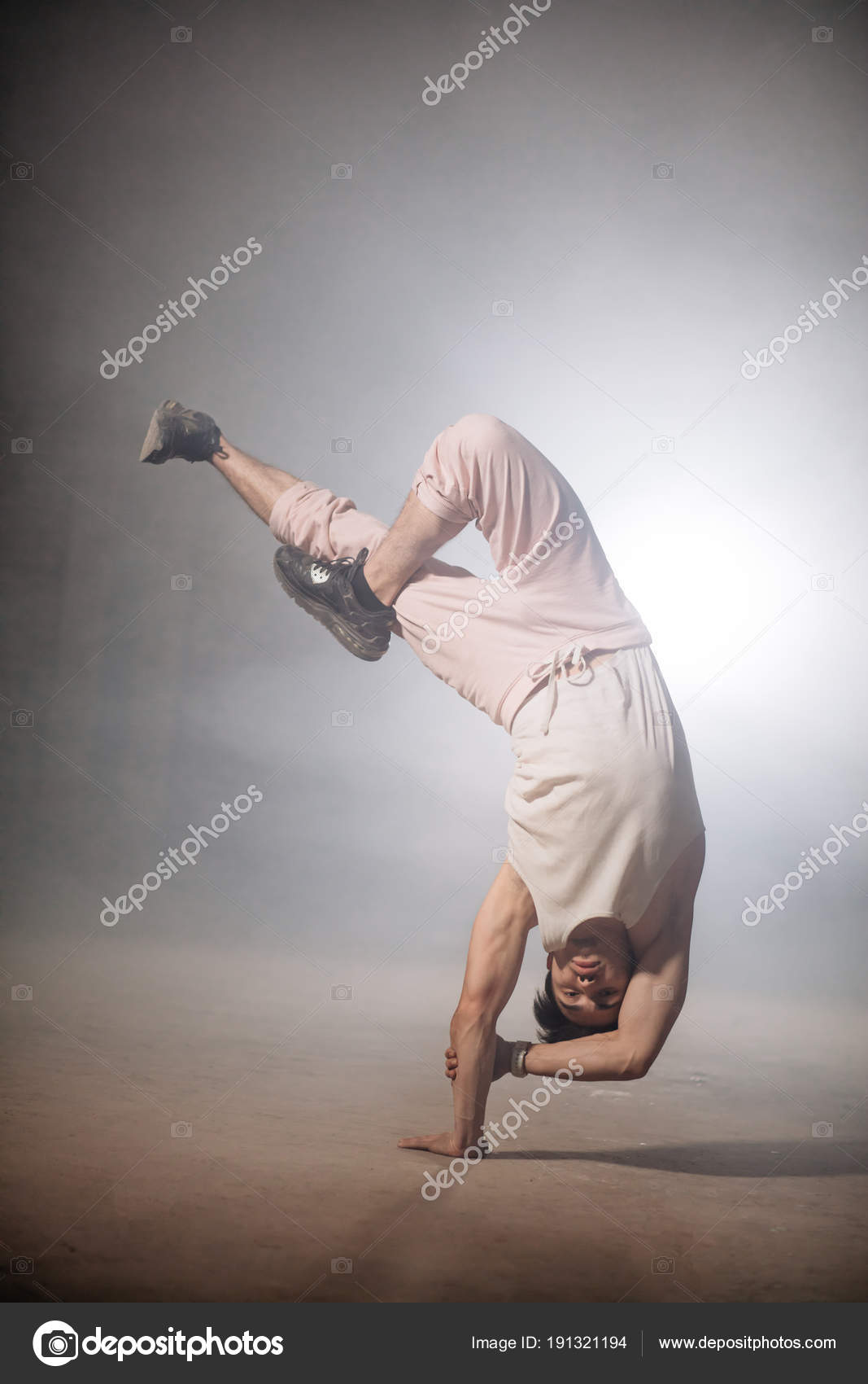 Man With Strong Muscles On Arms Doing Upside Down Stunt Stock