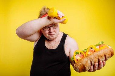 Fatigued fat man sweats while lifting burger