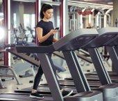 Junge Sportlerin nutzt Smartphone beim Joggen auf Laufband