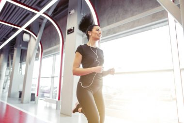 woman with earphones running on indoor track at gym