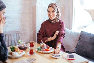 Two Muslim women in cafe, friends meeting