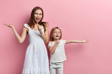 Excited cheerful happy mother and little daughter enjoying singing