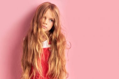 Shaggy little girl with long hair looking side isolated over pink background