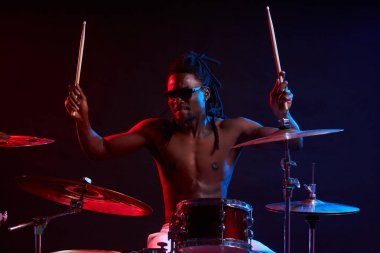active african man playing on drums set in neon lights