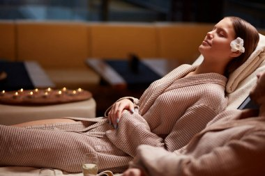 beautiful woman relaxing at spa salon, wearing bathrobe