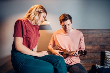 Handsome caucasian man playing ukulele guitar with beautiful woman in bedroom