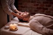 Muž dostává masáž obličeje v lázeňském salonu krásy