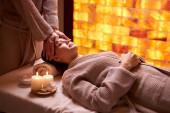 Kavkazská mladá žena dostává masáž obličeje v lázních