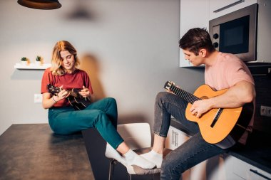 caucasian boy play guitar and woman play ukulele in kitchen