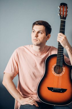 Portrait of young nice caucasian man posing with guitar isolated