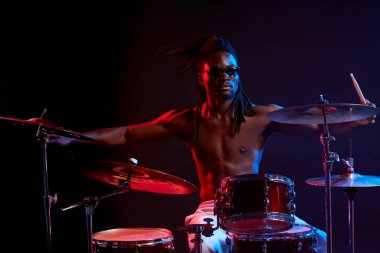 expressive artictic black man playing drums isolated over neon background