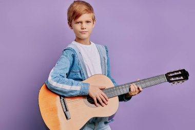 portrait of attractive little boy holding guitar isolated over purple background
