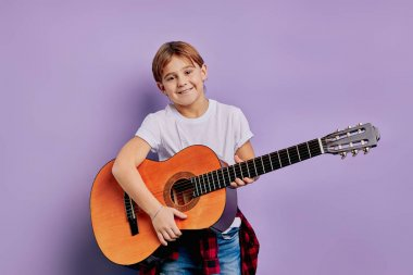 smiling boy playing the guitar isolated over purple background