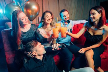 group of young people singing into microphone at party,celebrating birthday, karaoke
