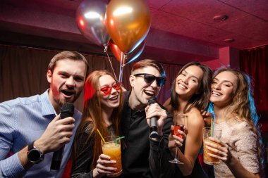 group of young people have party, holiday, relax and celebration in karaoke