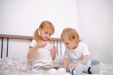 sweet caucasian children use modern gadget, holding tablet in hands
