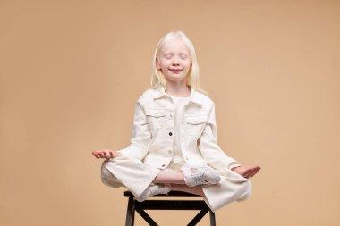 unusual alien albino child sit in yoga pose isolated
