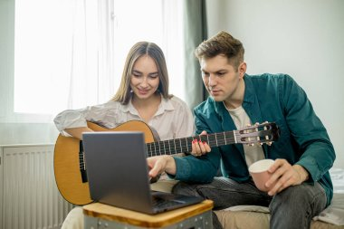 attractive caucasian couple watch lessons of playing guitar using laptop