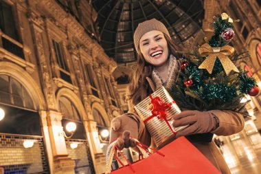 woman with Christmas tree showing shopping bags in Milan