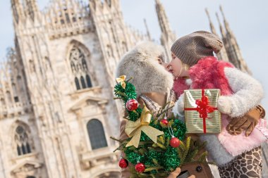 mother and daughter with Christmas tree and gift kissing. Milan