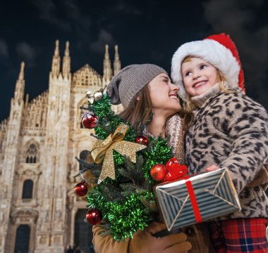 smiling mother and daughter with Christmas tree and gift. Milan