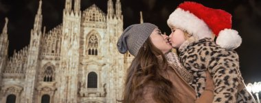 modern mother and child in Christmas hat in Milan, Italy kissing