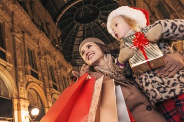 mother and child travellers with Christmas present box in Milan