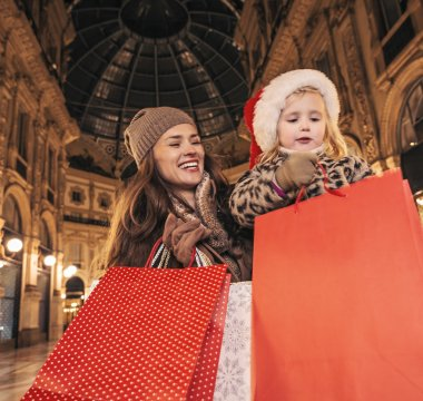 happy mother and daughter with Christmas shopping bags in Milan